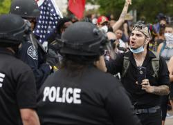 A participant in a protest over the death of George Floyd squares off with Denver Police officers Friday, May 29, 2020,