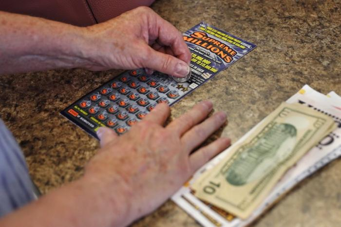A woman scratches a $30 instant ticket while playing the lottery at Ted's Stateline Mobil on Wednesday, June 24, 2020 in Methuen, Mass.