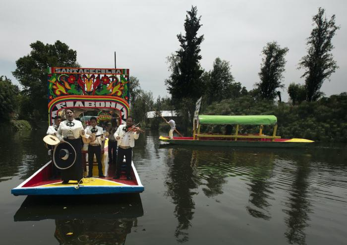 Mariachis perform on one of the painted wooden boats, known as a trajinera.