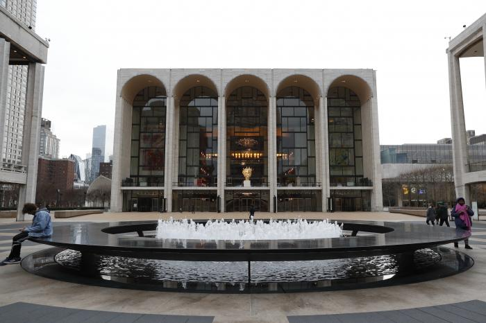 People by the fountain at Josie Robertson Plaza in front of The Metropolitan Opera house at Lincoln Center in New York.