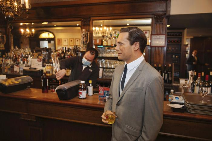 A wax statue of actor John Hamm stands by the bar with a drink at Peter Luger Steakhouse on Friday, Feb, 26, 2021, in New York.