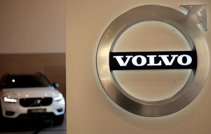 In this Feb. 6, 2020 file photo a Volvo car is parked behind the Volvo logo in the lobby of the company's corporate headquarters, in Brussels