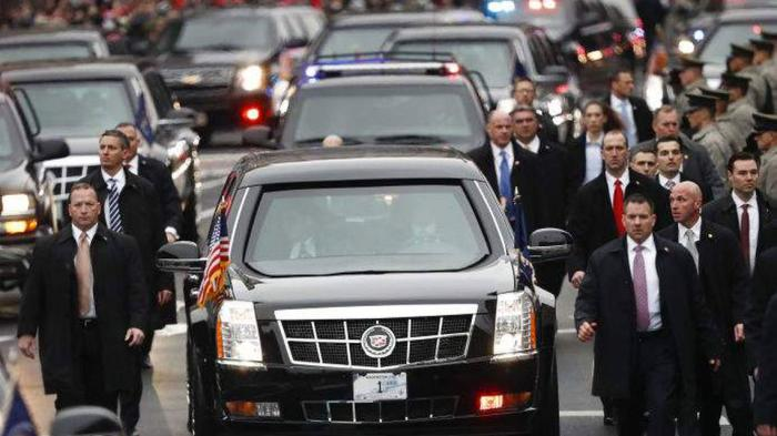 Members of President Donald Trump's Secret Service detail walk with the first family's motorcade vehicle as they move along the Inauguration Day parade route on January 20, 2017.