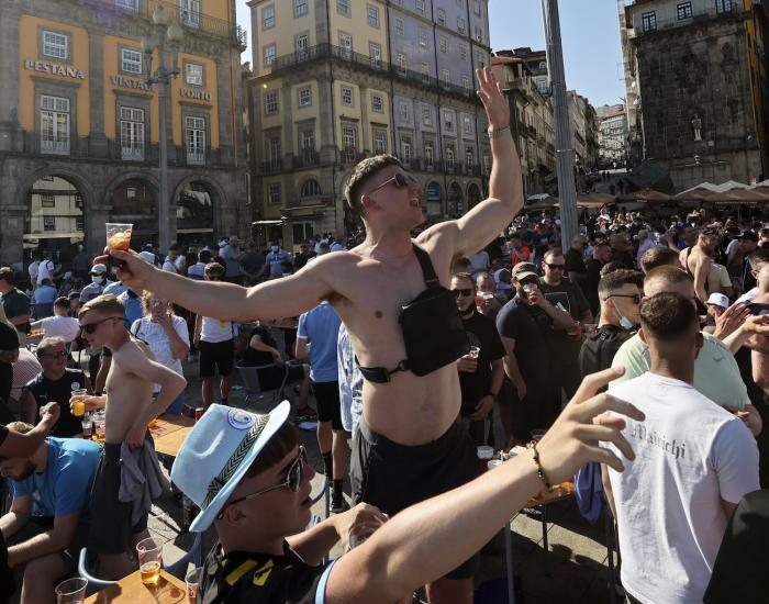 Manchester City supporters drink and chant by the Douro river bank in Porto, Portugal.