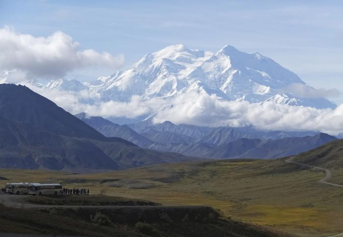 In this Aug. 26, 2016, file photo sightseeing buses and tourists are seen at a pullout popular for taking in views of North America's tallest peak, Denali, in Denali National Park and Preserve, Alaska.