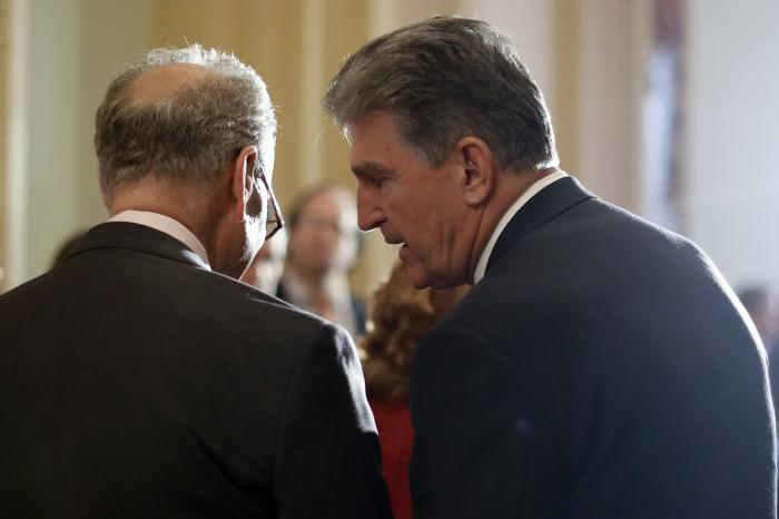 Sen. Joe Manchin, D-W.Va., right, speaks to then-Senate Minority Leader Charles Schumer, D-N.Y. during a news conference on Capitol Hill in Washington.