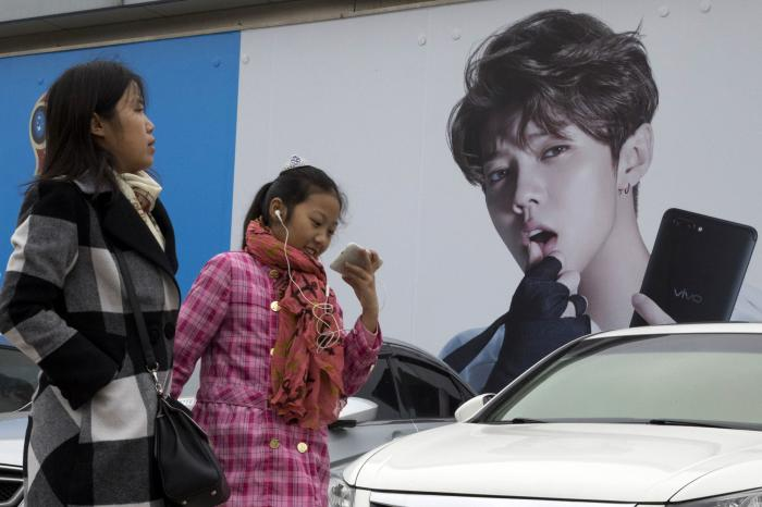 Chinese women walk past advertisement featuring teen idol Lu Han, also known as China's Justin Bieber in Beijing.