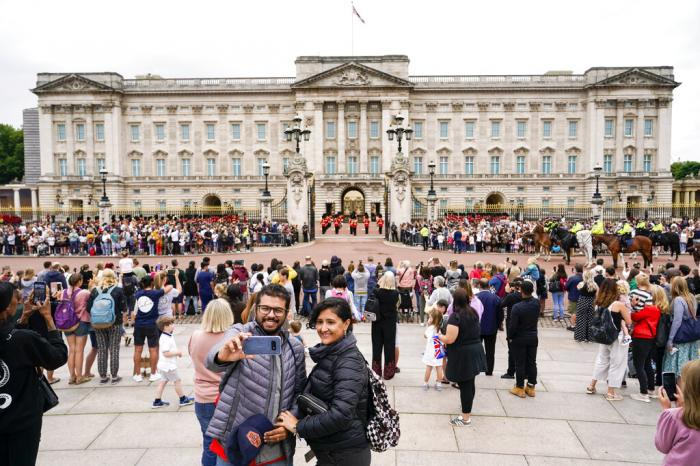 Members of the public watch the Changing of the Guard ceremony at Buckingham Palace, London.